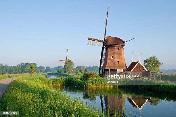 dutch windmills along canal - old windmill stock photos and pictures