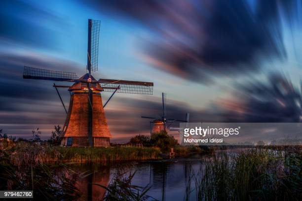 dutch windmills of kinderdijk on riverbank at sunset, kinderdijk, south holland, netherlands - dutch windmill stock photos and pictures