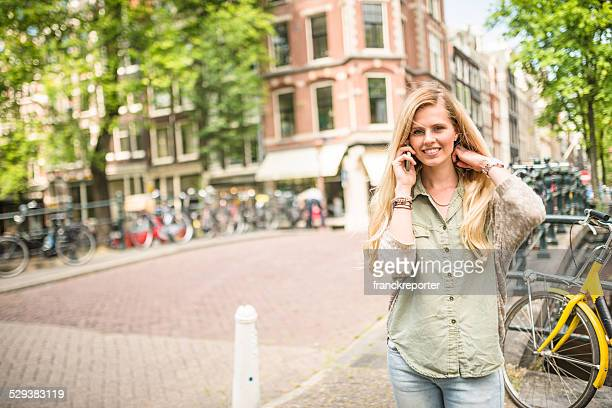 Dutch woman with bicycle in amsterdam on the phone