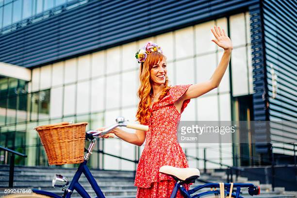 dutch woman with ginger hair and bicycle waving to friends - waving gesture stock photos and pictures
