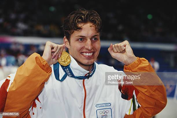 Dutch world record holding swimmer Pieter van den Hoogenband celebrates with his gold medal for the Netherlands team after finishing in first place...