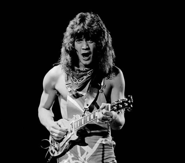 Dutch-born American musician Eddie Van Halen, of the group Van Halen, plays guitar as he performs onstage during US Festival concert, Devore,...