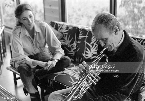 Dutch-born businesswoman and former model Wilhelmina Cooper watches as her husband, former television executive Bruce Cooper , plays the trumpet in...