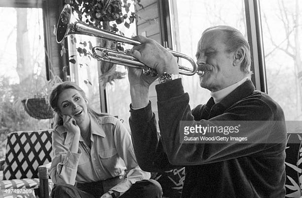 Dutchborn businesswoman and former model Wilhelmina Cooper watches as her husband former television executive Bruce Cooper plays the trumpet in the...