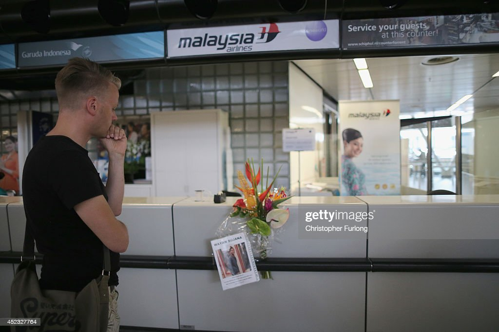 Dutchman Arthur Laumann pauses for thought after placing a floral tribute and photograph of Indonesian man Wayan Sujana of Bali, believed to be missing on Malaysia Airlines flight MH17, is fixed to the ticketing desk of Malaysia Airlines at Schiphol Airport on July 18, 2014 in Amsterdam, Netherlands. Malaysia Airlines flight MH17 travelling from Amsterdam to Kuala Lumpur crashed yesterday on the Ukraine/Russia border near the town of Shaktersk. The Boeing 777 was carrying 298 people including crew members, the majority of the passengers being Dutch nationals, believed to be at least 173, 44 Malaysians, 27 Australians, 12 Indonesians and 9 Britons. It has been speculated that the passenger aircraft was shot down by a surface to air missile by warring factions in the region.
