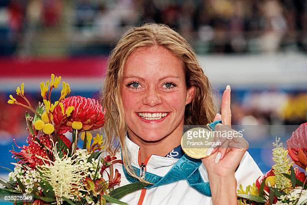 Dutchman Inge de Bruijn shows off the gold medal she won in the women's 100meter butterfly final at the Sydney Olympics