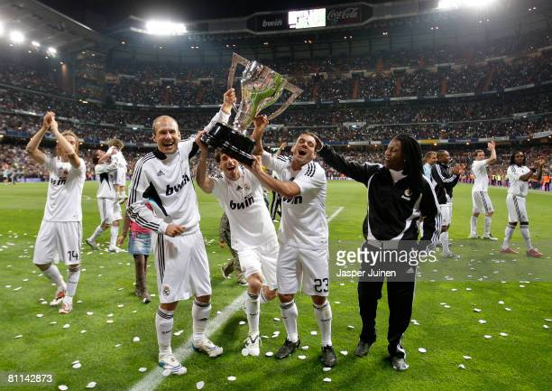 Dutchmen Arjen Robben Ruud van Nistelrooy and Wesley Sneijder of Real Madrid hold alloft the La Liga trophy flanked by their teammate Royston Drenthe...