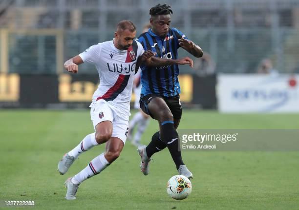 Duvan Zapata of Atalanta BC is challenged by Danilo Larangeira of Bologna FC during the Serie A match between Atalanta BC and Bologna FC at Gewiss...