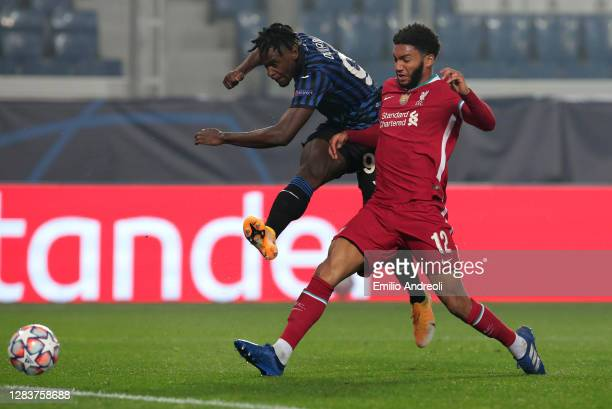 Duvan Zapata of Atalanta BC is challenged by Joe Gomez of Liverpool FC during the UEFA Champions League Group D stage match between Atalanta BC and...