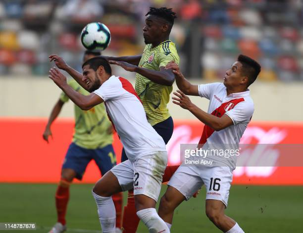 Duvan Zapata of Colombia and Luis Abram and Jesus Pretell of Peru in action during a friendly match between Peru and Colombia at Estadio Monumental...