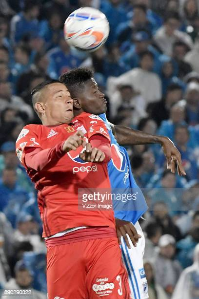 Duver Riascos of Millonarios jumps for a header with Anderson Zapata of America de Cali during the second leg match between Millonarios and America...