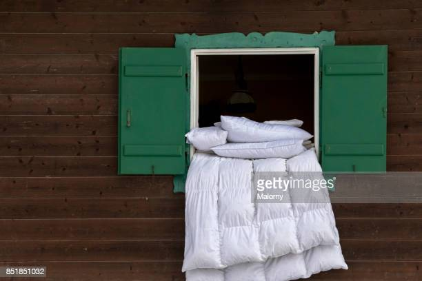 duvet airing on the ledge of an open green window of a log cabin - duvet stock pictures, royalty-free photos & images