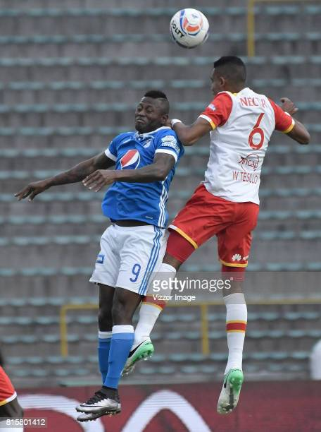 Duvier Riascos of Millonarios jumps for a header with William Tesillo of Independiente Santa Fe during the match between Millonarios and...