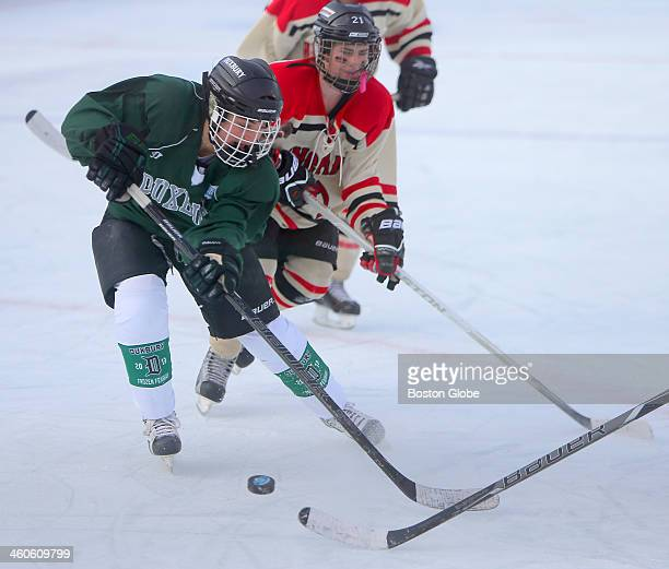 Duxbury High School's Jane Dudley vies with Hingham High School's Alissa Sullivan in the second period as the girls' hockey teams face off at frozen...