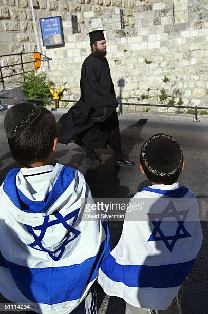 Dvir Bakri sixyearsold and his brother Amir fiveyearsold from Jerusalem wear Israeli flags as they watch a GreekOrthodox priest pass the Old City...