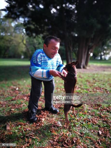 Dwarf Man Playing With Dog At Park