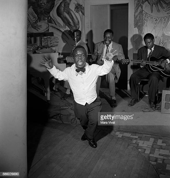 A dwarf man tap dances to a band in a New Orleans jazz club Louisiana USA