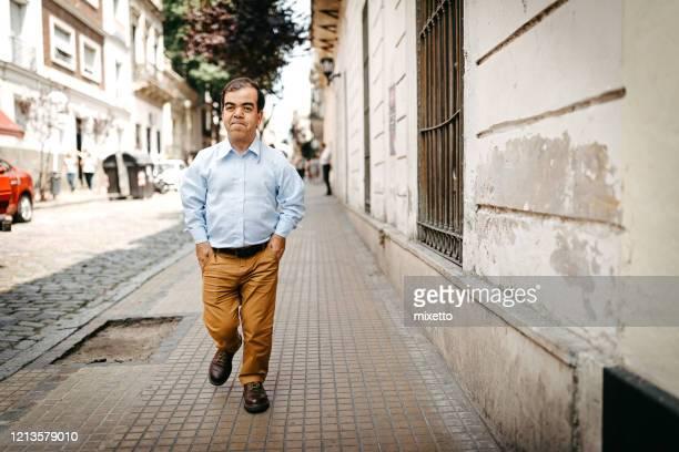 dwarf man walking on city street - dwarf man stock pictures, royalty-free photos & images