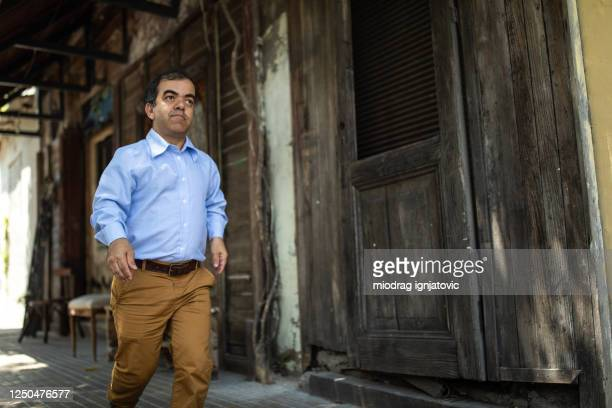 dwarfish businessman on his way to home after work - dwarf man stock pictures, royalty-free photos & images