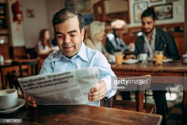 dwarfish man reading newspaper at cafe - dwarf man stock pictures, royalty-free photos & images