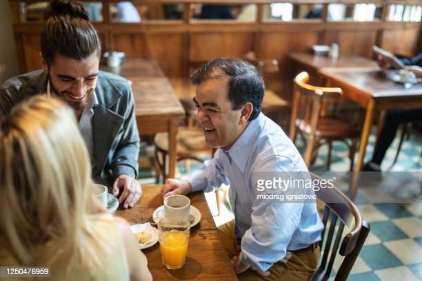 dwarfish man spending quality time with friends at local cafe - dwarf man stock pictures, royalty-free photos & images