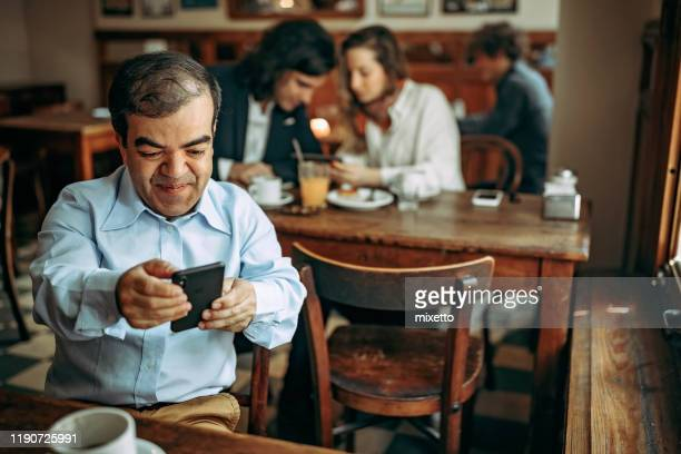 dwarfish man using mobile phone at cafe - dwarf man stock pictures, royalty-free photos & images