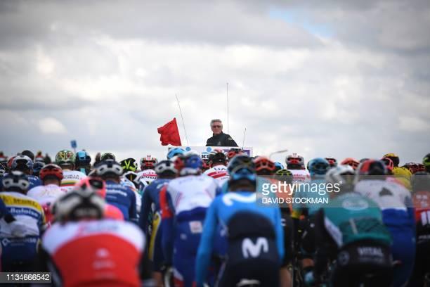 TOPSHOT Dwars door Vlaanderen Race's director Scott Sunderland looks on as pack rides during the 74th edition of the Dwars Door Vlaanderen cycling...