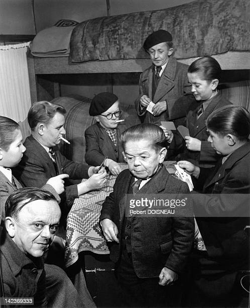 Dwarves working at the Pinder Circus playing cards and smoking in their room Paris France in 1949