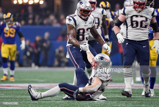 Dwayne Allen of the New England Patriots helps Rex Burkhead up off the ground in the second half during Super Bowl LIII at MercedesBenz Stadium on...