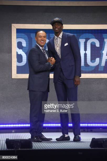 Dwayne Bacon shakes hands with Deputy Commissioner Mark Tatum after being selected number forty overall by the New Orleans Pelicans during the 2017...