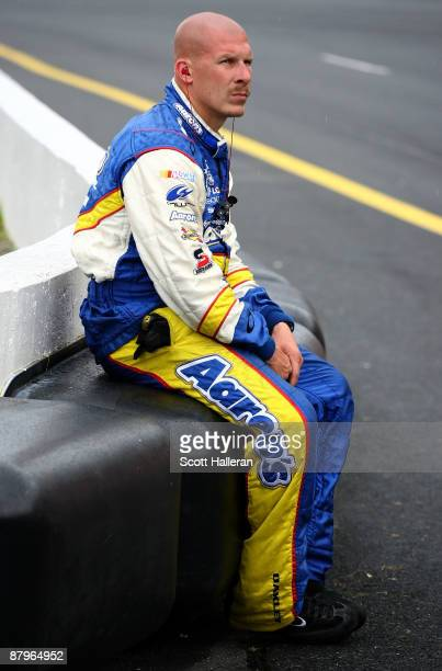 Dwayne Bigger, crew member for the Aaron's Dream Machine Toyota, sits on pit road during a rain delay during the NASCAR Sprint Cup Series Coca-Cola...