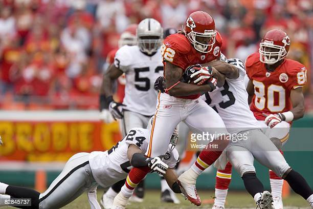 Dwayne Bowe of the Kansas City Chiefs is tackled by DeAngelo Hall the Oakland Raiders at Arrowhead Stadium on September 14 2008 in Kansas City...