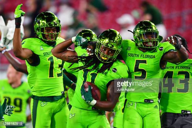Dwayne Boyles celebrates with Tramel Logan and Antonio Grier of the South Florida Bulls after Boyles intercepted a pass thrown by Dillon Gabriel of...