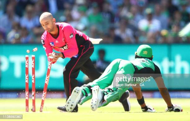 Dwayne Bravo of the Stars is run out by Nathan Lyon of the Sixers during the Big Bash League match between the Melbourne Stars and the Sydney Sixers...