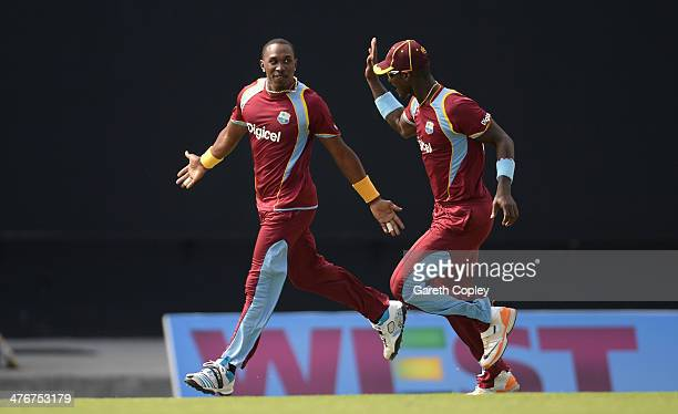 Dwayne Bravo of the West Indies celebrates with Darren Sammy after dismissing Ben Stokes of England during the 3rd One Day International between the...