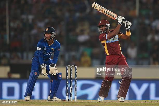 Dwayne Bravo of the West Indies hits the ball towards the boundary as Kumar Sangakkara of Sri Lanka looks on during the ICC World Twenty20 Bangladesh...