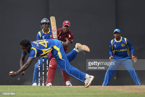 Dwayne Bravo of West Indies looks on as Ajantha Mendis of Sri Lanka fields off his own bowling during the 2011 ICC World Cup warm up match between...