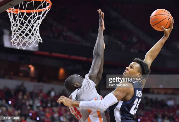 Dwayne Brown Jr #25 of the Utah State Aggies goes up for a dunk attempt against Cheikh Mbacke Diong of the UNLV Rebels during their game at the...