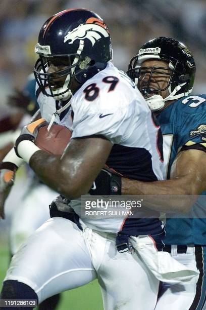 Dwayne Carswell of the Denver Broncos runs by Carnell Lake of the Jacksonville Jaguars after a first quarter reception 13 December 1999 at Alltell...