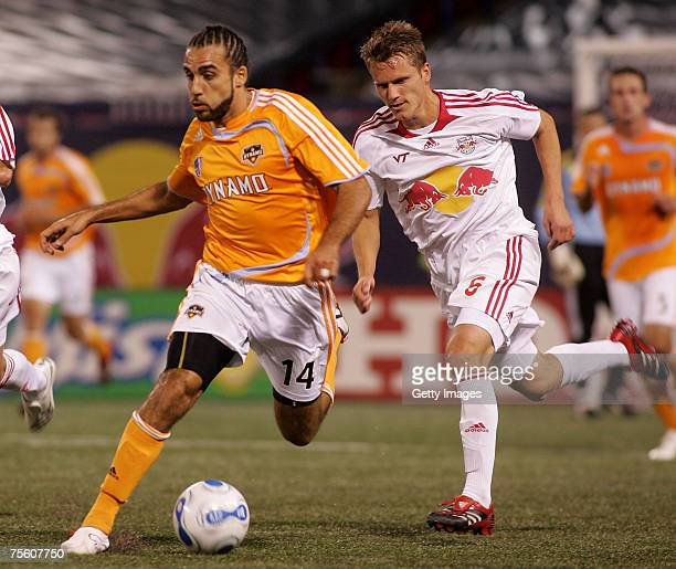 Dwayne De Rosario of the Houston Dynamo plays the ball down the field against Seth Stammler#6 of the New York Red Bulls at Giants Stadium in the...