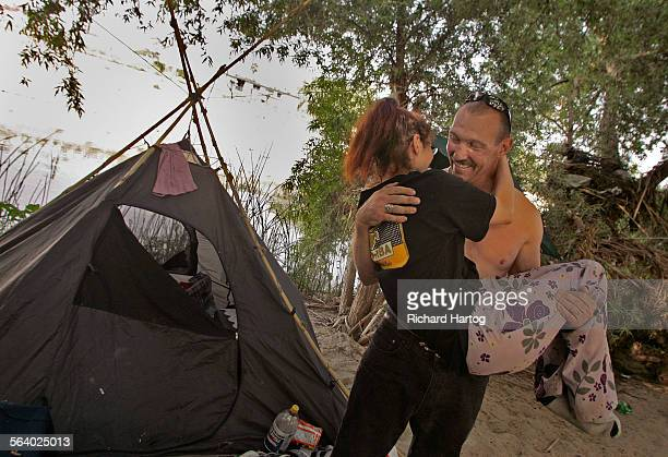 Dwayne Dickinson, right, and girlfriend Melissa Millner share a tender moment outside the tent that they call home during a look at the homeless...