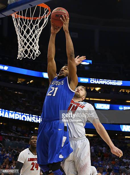 Dwayne Evans of the Saint Louis Billikens goes up to dunk over Stephan Van Treese of the Louisville Cardinals in the first half during the third...