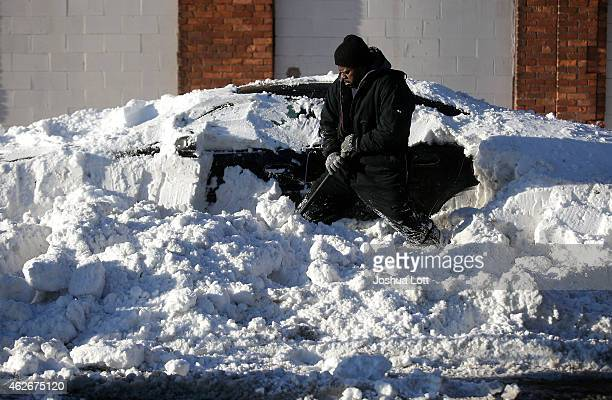 Dwayne Goings digs out a vehicle buried in snow with his shovel February 2 2015 in Detroit Michigan Detroit received over a foot of snow during a...