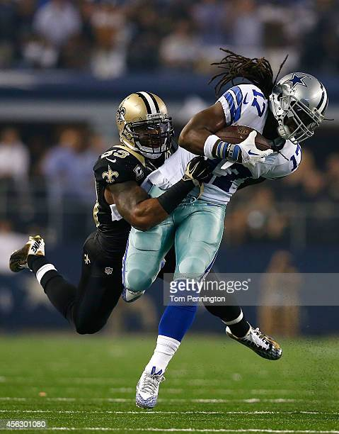Dwayne Harris of the Dallas Cowboys carries the ball as Ramon Humber of the New Orleans Saints tries to make the tackle in the first half at ATT...