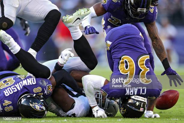 Dwayne Harris of the Oakland Raiders is tackled by inside linebacker Patrick Onwuasor and defensive back Chuck Clark of the Baltimore Ravens during...