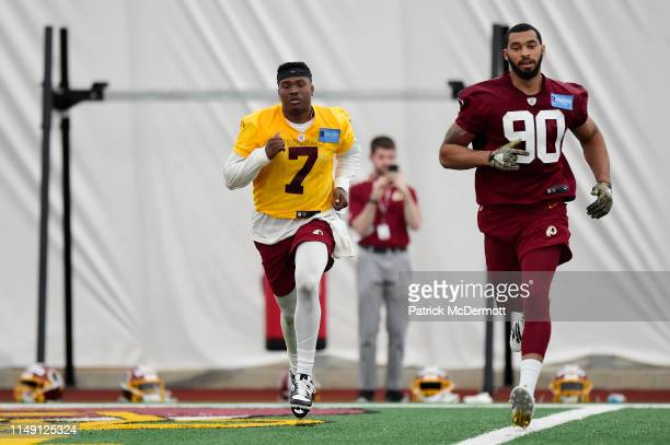 Dwayne Haskins Jr #7 and Montez Sweat of the Washington Redskins take part in a drill during Washington Redskins rookie camp on May 11 2019 in...