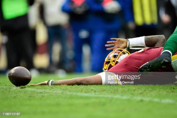 Dwayne Haskins of the Washington Redskins loses the ball after being sacked by Frankie Luvu and James Burgess of the New York Jets during the second...