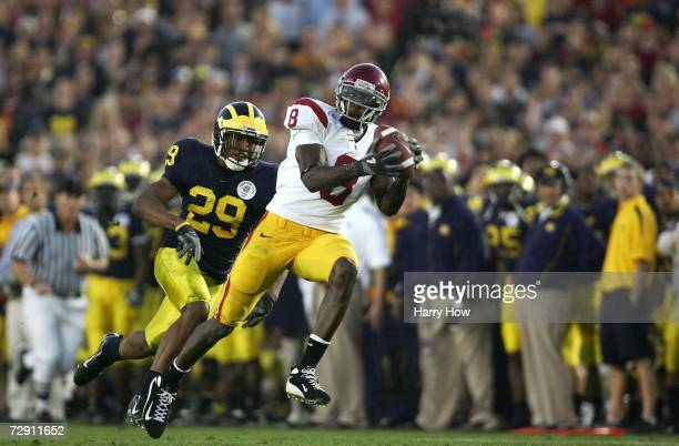 Dwayne Jarrett of the USC Trojans makes a catch and runs in a touchdown in front of Leon Hall of the Michigan Wolverines during the fourth quarter of...