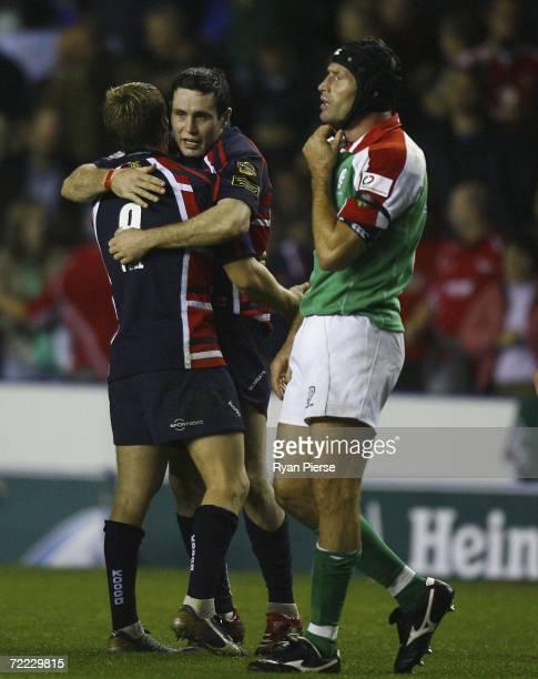 Dwayne Peel and Stephen Jones of Scarlets celebrate as Phil Murphy of London Irish looks dejected after the Heineken Cup Pool 5 match between London...