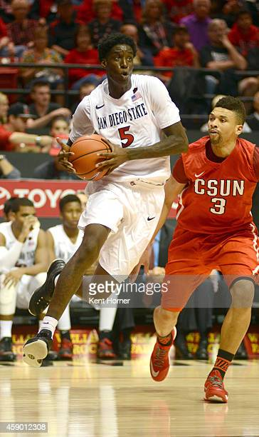 Dwayne Polee of the San Diego State Aztecs drives to the basket with the ball in the second half of the game against Stephan Hicks of the Cal-State...